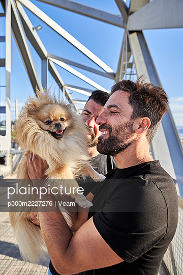 Homosexual couple with dog on footbridge during sunny day - p300m2227276 by Veam