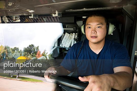 Chinese fireman wearing headphones driving fire truck