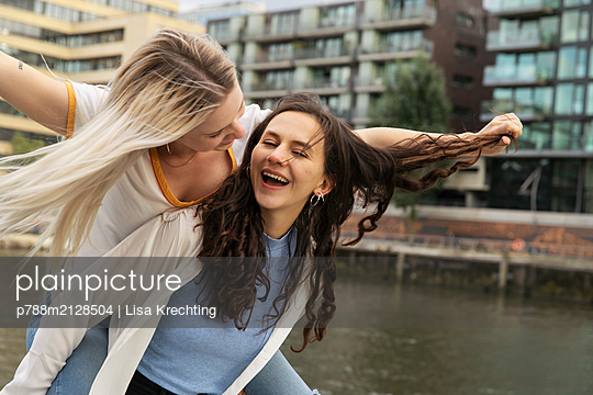 Young woman gives girlfriend a piggyback ride - p788m2128504 by Lisa Krechting