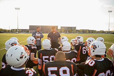 Coaches talking to teenage boy high school football team before game on sunny football field - p1192m1500248 by Hero Images