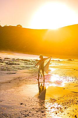 Frau tanzt am Strand bei Sonnenuntergang - p1455m2203715 von Ingmar Wein