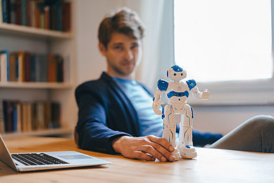 Man sitting at table with robot - p300m1588012 by Kniel Synnatzschke