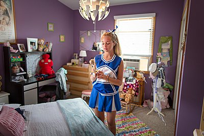Cheerleader holding trophy in bedroom - p429m1084529 by Steve Prezant