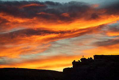 Lone figure on hill watching dramatic sunset, Ait Benhaddou, Morocco, North Africa, Africa - p871m2209264 by Ed Rhodes