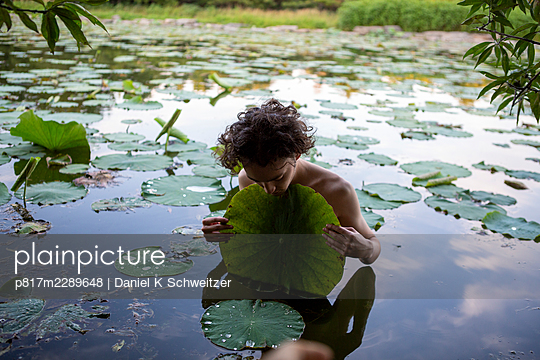 Young man in a pond holding giant lily pad - p817m2289648 by Daniel K Schweitzer