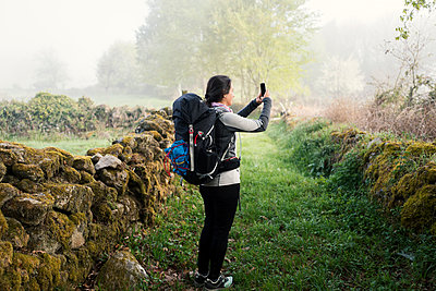 Woman walking the way of Saint James using smartphone - p1165m1441858 by Pierro Luca