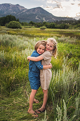 Portrait of happy sisters embracing while standing on grassy field in forest during sunset - p1166m2024958 by Cavan Images