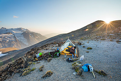 Man pokes head out of tent at sunset while camping on mountain ridge. - p1166m2153415 by Cavan Images