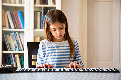 Girl playing roll piano at home - p300m2188858 by Larissa Veronesi