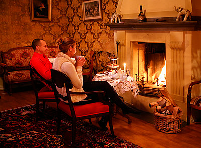 Man and woman relaxing by fireplace - p312m1338765 by Lena Granefelt