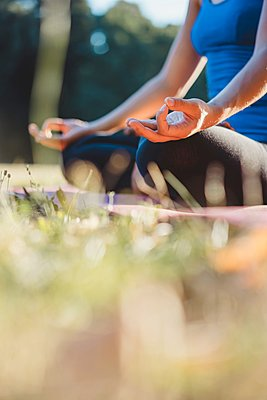 Mature woman in park, sitting in yoga position, low angle view - p429m1494174 by Arno Images