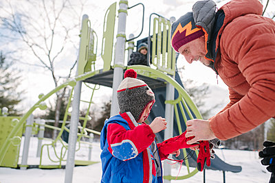 Father putting on boy's gloves by playground slide in snow - p924m2074500 by Viara Mileva