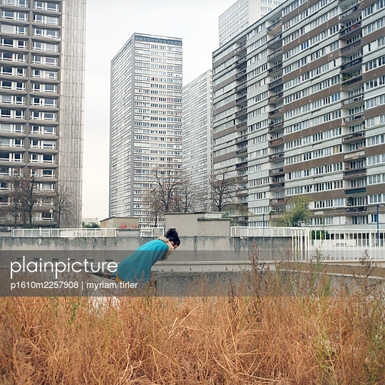 A woman at the bottom of a block of flats - p1610m2257908 by myriam tirler