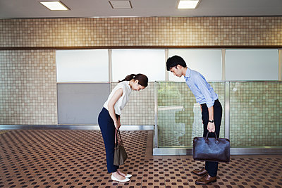 Two people greeting, a man and young woman bowing from the waist when they meet in a subway.  - p1100m1531121 by Mint Images