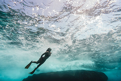 Low angle view of woman diving undersea - p1166m2067153 by Cavan Images