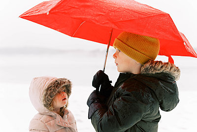 A brother and sister having fun in the wintery rain. - p1166m2157466 by Cavan Images