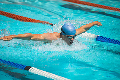 Young Caucasian male swimmer swimming butterfly stroke in outdoor swimming pool - p1315m2091023 by Wavebreak