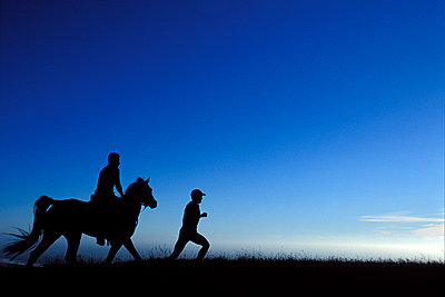 Silhouette of a person running with another person riding a horse behind. - p1424m1501075 by Corey Rich