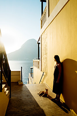 Greece, Kalymnos, Young woman leaning on yellow wall - p352m1186951 by Lena Katarina Johansson