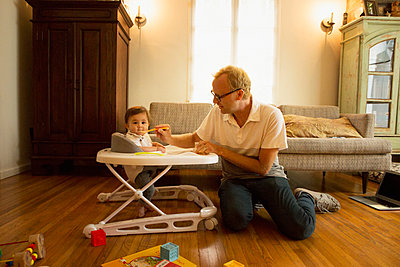 Father feeding son in high chair in living room - p555m1410931 by Lucy von Held