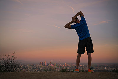 Rear view of jogger stretching at dusk, Runyon Canyon, Los Angeles, California, USA - p924m1422787 by Raphye Alexius