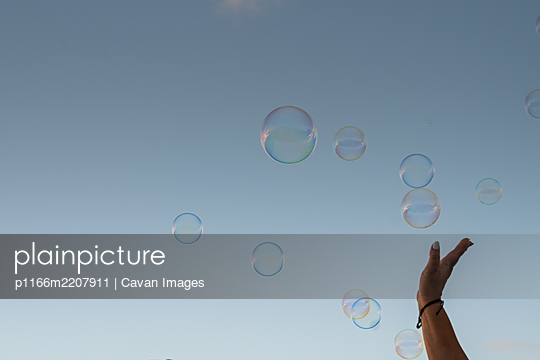 a hand tries to touch bubbles in the sky - p1166m2207911 by Cavan Images