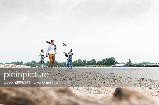 Happy father with two sons and football walking at the riverside - p300m2005344 von Uwe Umstätter
