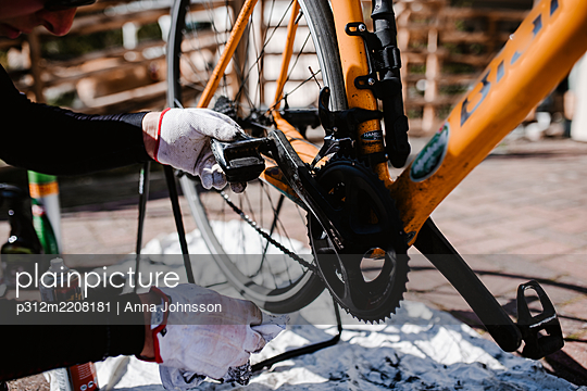 Person repairing bicycle - p312m2208181 by Anna Johnsson