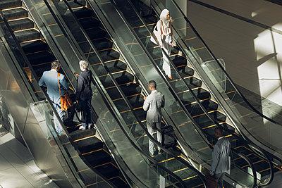 Business people using escalators in modern office  - p1315m2117972 by Wavebreak