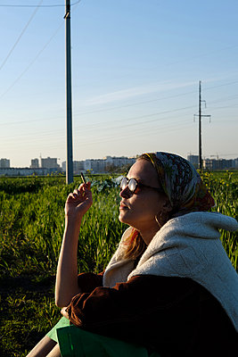 Young woman smoker with cigarette sitting in field on the outskirts of the city - p1363m2013495 by Valery Skurydin