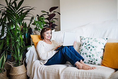 Smiling woman using laptop while sitting on sofa at home - p300m2265653 by Eva Blanco