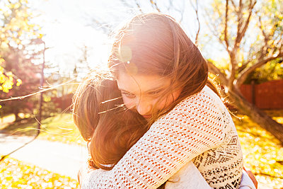 Two sisters hugging each other in a city park on a warm autumn day: Edmonton, Alberta, Canada - p442m2101135 by LJM Photo