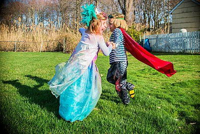 Children in costumes playing outdoors - p924m1067496f by Sue Barr