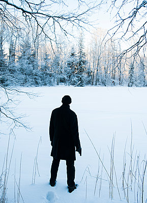 Man with a gun standing in snowy landscape - p971m1094173 by Reilika Landen