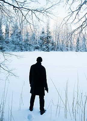 Man with a gun standing in snowy landscape - p971m1094173 by Reilika Landen