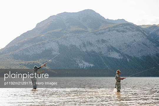 Mother and son fly fishing in sunny lake - p1192m2129175 by Hero Images