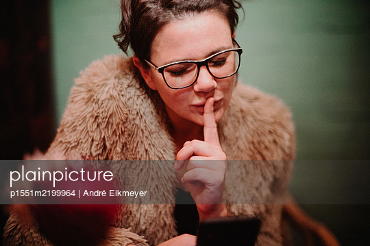 Woman touches mouth with index finger - p1551m2199964 by André Eikmeyer