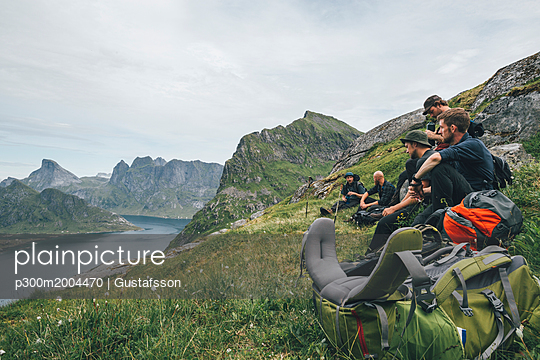 Norway, Lofoten, Moskenesoy, Group of young men sitting on grass, looking over Kjerkefjord - p300m2004470 von Gustafsson