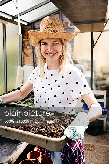 Young woman gardening in a greenhouse - p300m2103551 by Epiximages
