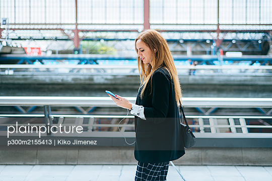 Young woman with earphones and cell phone on the go at train station - p300m2155413 by Kiko Jimenez