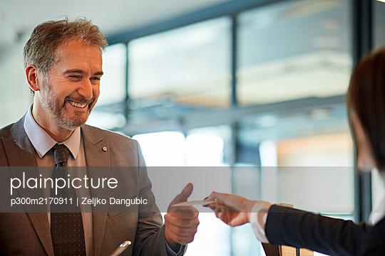 Portrait of smiling businessman checking in at hotel reception - p300m2170911 by Zeljko Dangubic
