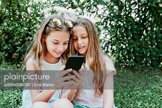 two kid girls sittingon grass and using mobile phone, summertime, Madrid, Spain - p300m2287297 von Eva Blanco