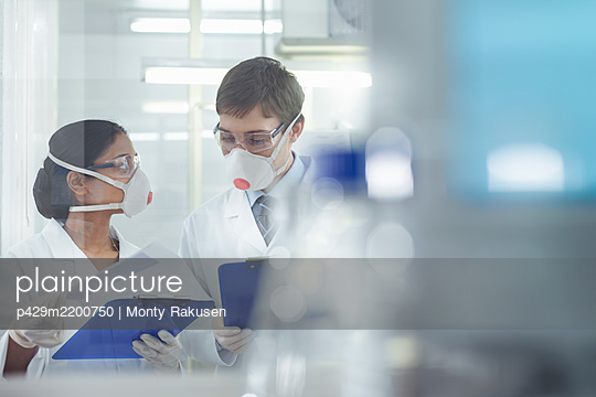 Scientists in isolation environment wearing masks, working in research laboratory. - p429m2200750 by Monty Rakusen
