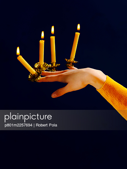 Woman with four candlesticks and candles on her fingers - p801m2257694 by Robert Pola