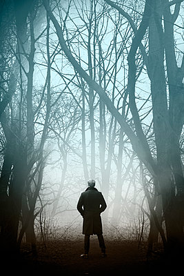 Man in black coat standing in the forest - p1248m2200411 by miguel sobreira