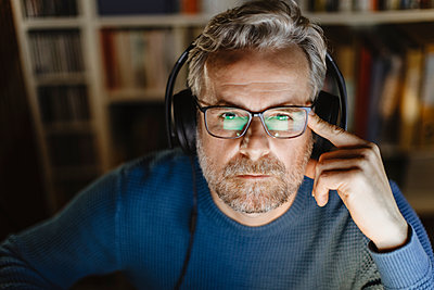 Portrait of pensive mature man with headphones in front of computer - p300m2180486 by 27exp