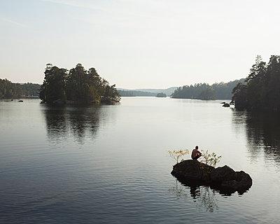 Sweden, Blekinge, Man crouching on rock on Lake Halen - p352m1142185 by Gustaf Emanuelsson