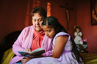 Hispanic grandmother and granddaughter reading book on bed - p555m1409593 by Shestock