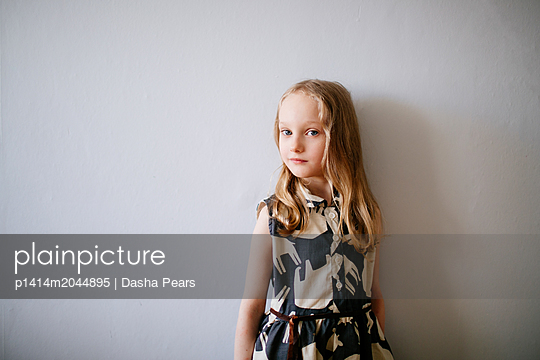 Blonde girl standing by a wall - p1414m2044895 by Dasha Pears