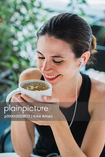 Young businesswoman sitting in coffee shop, taking a break, drinking tea - p300m2023872 von Kike Arnaiz